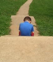 Child sit on sidewalk